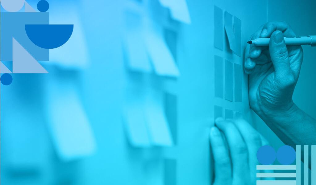 A imagem mostra um quadro de acompanhamento de fluxo de trabalho com papéis colados na parede e anotações